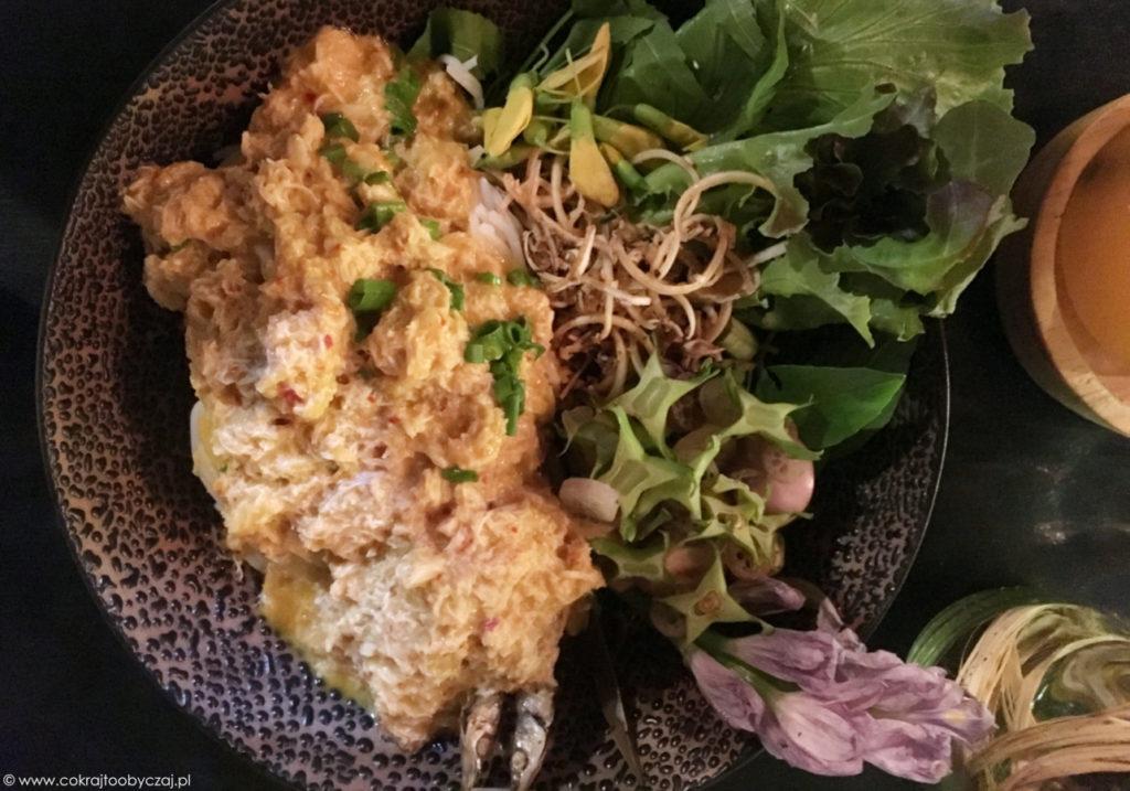 Makaron z rybno-krabowym sosem curry w towarzystwie kwiatów i zieleniny.
