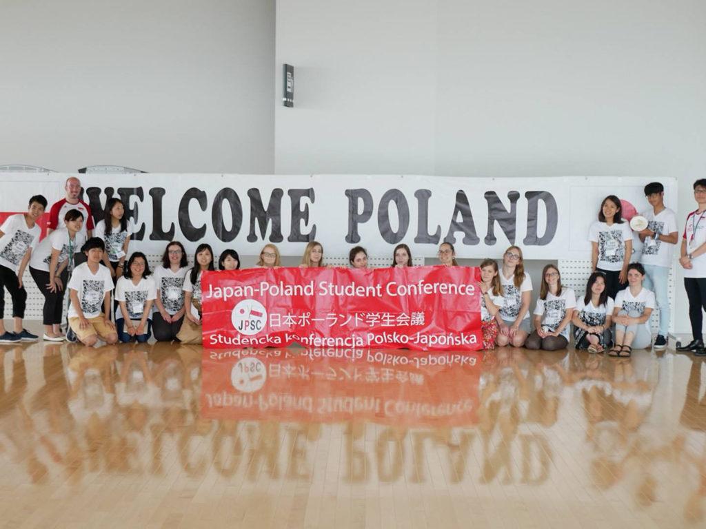 Nasza grupa w Takasaki Arena. Stoimy na tle tego samego baneru, który widać na zdjęciu obok. Źródło: materiały organizatorów konferencji.