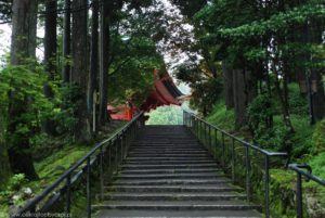 Schody i majaczący w tle czerwony dach zabudowań świątynnych Enryaku-ji.