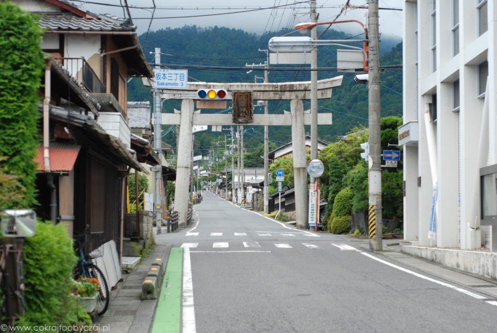 Uliczne światła na tle betonowej bramy tori w Otsu.