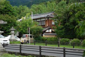 Stary, drewniany japoński dom z bambusowym lasem w tle.