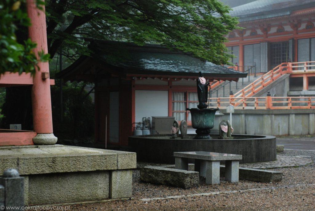Kamienny stolik, ławki i posągi przy buddyjskiej świątyni w Japonii.