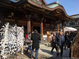 Omikuji zawiązane na drabince przy świątyni.