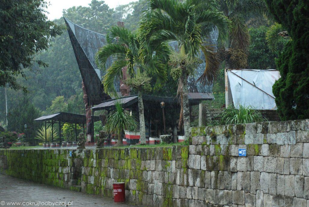 Ulewny deszcz i palmy wśród tradycyjnych domów Bataków Toba.