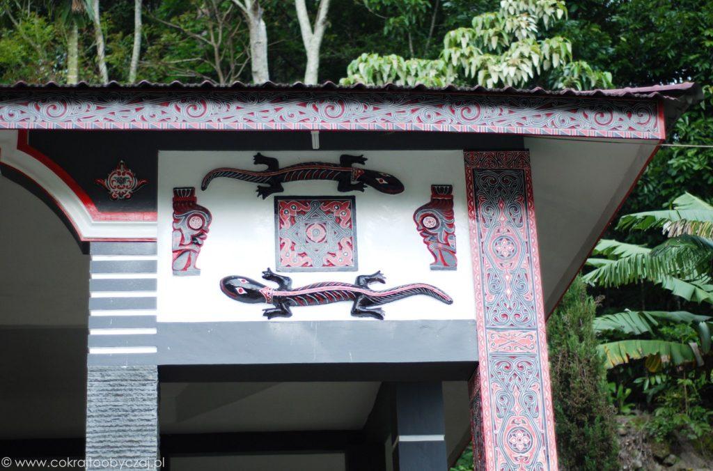 Czarno-czerwone dekoracyjne gekony na ścianie domu Bataków Toba.