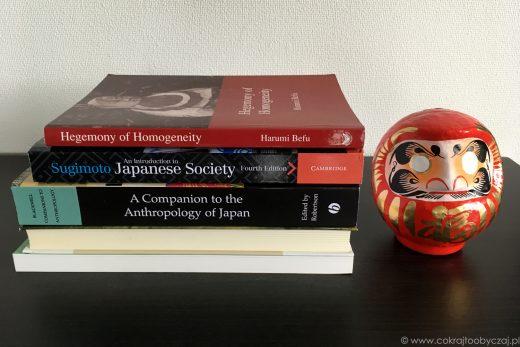 Antropologiczne książki o Japonii i figurka darumy.